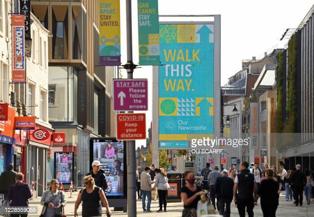 Pedestrians and shoppers, some wearing a face mask or covering, walk past signs alerting them to a one-way system in operation to help with social...