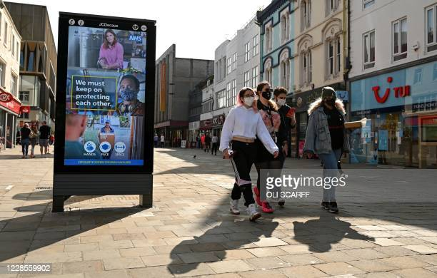 Pedestrians and shoppers, some wearing a face mask or coverings, walk past a an electronic billboard asking members of the public to follow the UK...