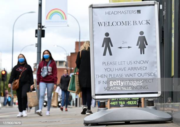 Pedestrians and shoppers, some wearing face masks as a precaution against the transmission of the novel coronavirus, walk in the high street in west...