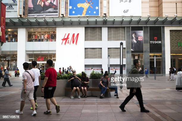 Pedestrians and shoppers walk past a Hennes Mauritz AB store on Wangfujing Street in Beijing China on Wednesday June 27 2018 Consumer sentiment in...