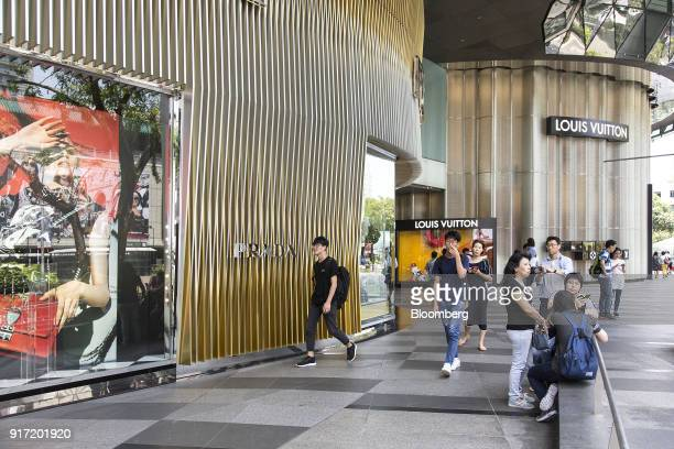 Pedestrians and shoppers walk past a Prada SpA luxury fashion store left as a Louis Vuitton store operated by LVMH Moet Hennessy Louis Vuitton SE...