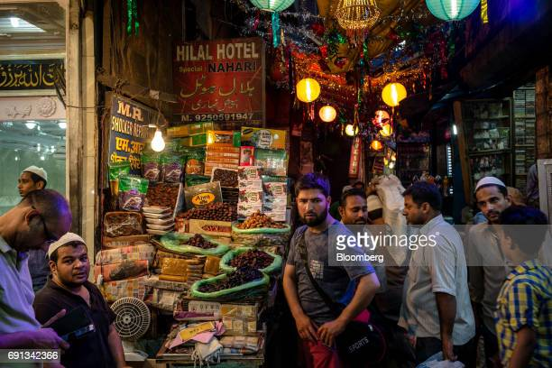Pedestrians and shoppers walk past a stall selling dates outside the Jama Masjid at night during the Muslim holy month of Ramadan in the Old Delhi...
