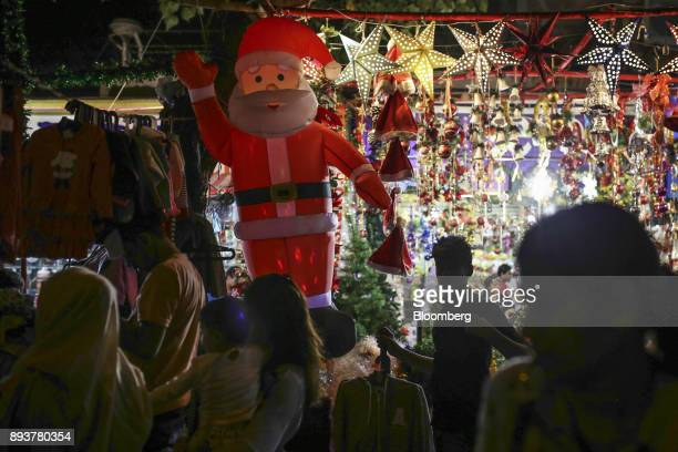 Pedestrians and shoppers walk past a stall selling festive Christmas decorations in Mumbai India on Friday Dec 15 2017 India's inflation surged past...