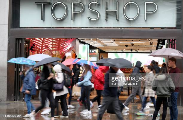 Pedestrians and shoppers walk past a Topshop and Topman store, operated by Arcadia, in London on June 12, 2019. - Landlords and other creditors were...