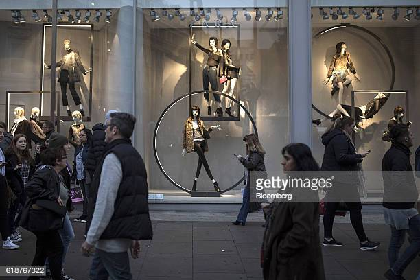 Pedestrians and shoppers walk past a window displaying fashion collections at a Zara fashion store a unit of Inditex SA on Oxford Street on Thursday...