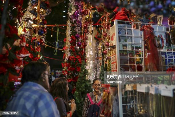 Pedestrians and shoppers walk past festive Christmas decorations displayed for sale at a stall in Mumbai India on Friday Dec 15 2017 India's...