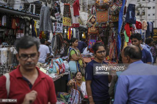 Pedestrians and shoppers walk past handbags on display at a roadside stall in Mumbai India on Friday Dec 15 2017 India's inflation surged past the...