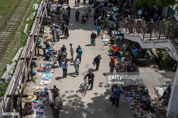 Pedestrians and shoppers walk past stalls at a market in Dushanbe Tajikistan on Sunday April 22 2018 Flung into independence after the Soviet Union...
