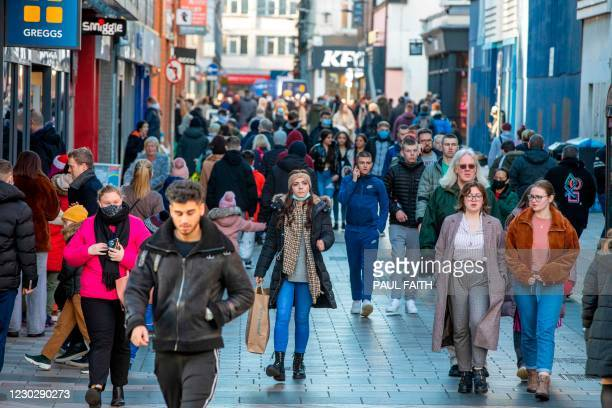 Pedestrians and shoppers walk through Belfast city centre on Christmas Eve, December 24, 2020 as the Province prepares to go into a six week...