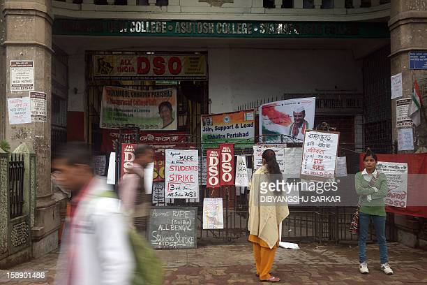 Pedestrians and students are seen in front of placards calling for a statewide student strike against rape in front of a government college in...