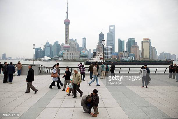 Pedestrians and tourists enjoy the newly rebuilt Bund or riverfront area in Shanghai China