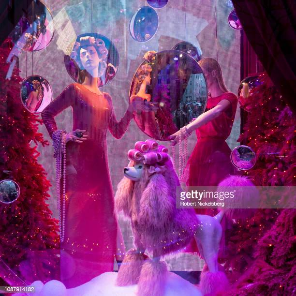Pedestrians and tourists have their pictures taken near the Broadway themed Theater of Dreams shop windows at Saks Fifth Avenue department store in...