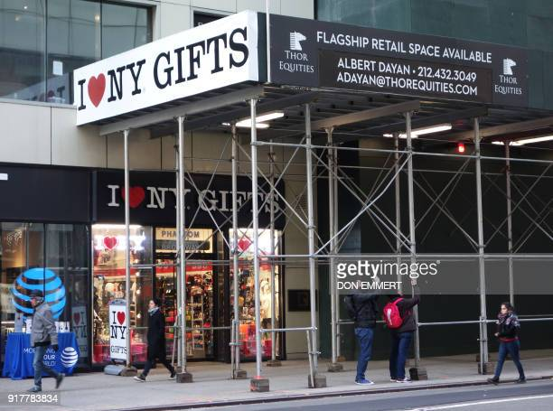 Pedestrians and tourists pass by a building with empty retail space on 5th Avenue on February 8 2018 in New York The New York borough of Manhattan is...