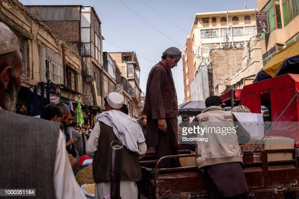 Pedestrians and traders walk past a man standing on the back of a pick up vehicle at Mandai Bazaar in Kabul Afghanistan on Thursday July 12 2018 US...