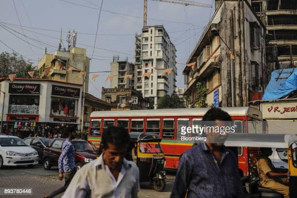 Pedestrians and traffic move past buildings in Mumbai India on Friday Dec 15 2017 India's inflation surged past the central bank's target bolstering...
