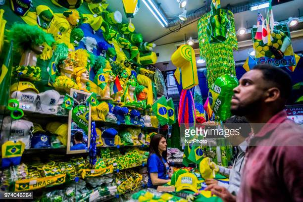 Pedestrians and traffic pass on a street decorated in Brazilian flags ahead of the FIFA World Cup games in downtown Sao Paulo Brazil onThrusday June...