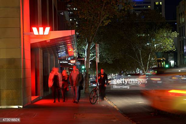 Pedestrians and traffic past a Westpac Banking Corp office building in this long exposure photograph taken at night in Melbourne Australia on Friday...
