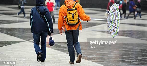 Pedestrians and umbrella in hard wind