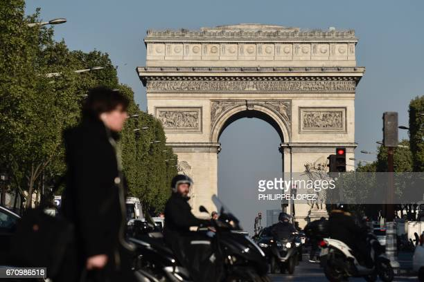 Pedestrians and vehicles take the Champs Elysees avenue near the Arc de Triomphe monument in Paris on April 21 a day after a gunman opened fire on...