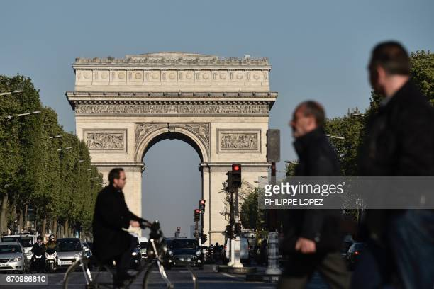 TOPSHOT Pedestrians and vehicles take the Champs Elysees avenue near the Arc de Triomphe monument in Paris on April 21 a day after a gunman opened...