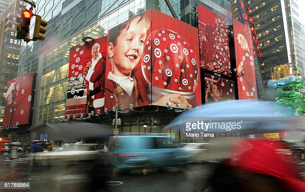 Pedestrians are blurred as they walk past a holiday advertisement for Target stores in Times Square November 24 2004 in New York City Retailers are...