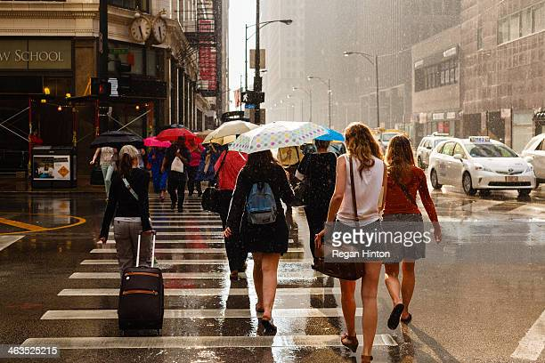 CONTENT] Pedestrians are caught in an afternoon rain shower in downtown Chicago