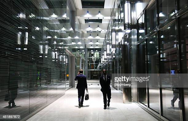Pedestrians are illuminated by electric lights as they walk through an underpass between buildings in the Canary Wharf business finance and shopping...