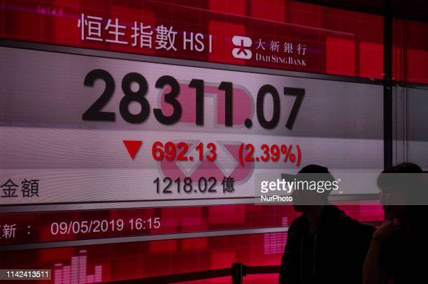 Pedestrians are is seen walking pass an electronic display board which shown the Hang Seng Index in Hong Kong China on May 10 2019