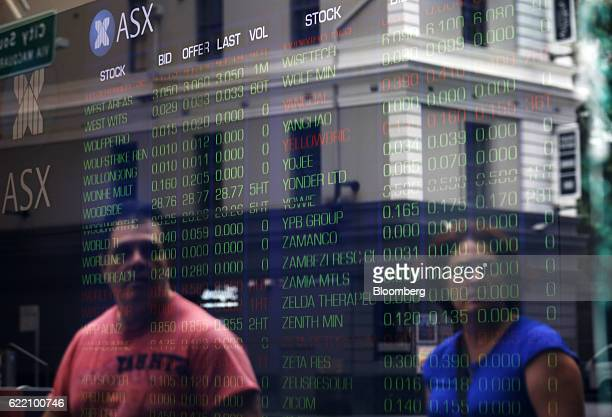 Pedestrians are reflected against an electronic board displaying stock information inside the Australian Securities Exchange operated by ASX Ltd in...