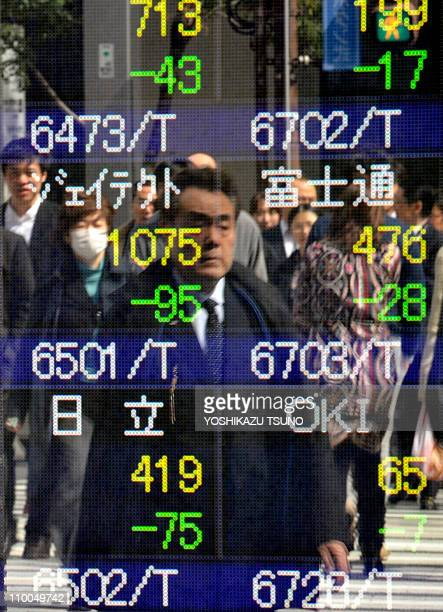 Pedestrians are reflected in a share prices board in Tokyo on March 14 2011 during the first full day of trading after the deadly March 11 earthquake...
