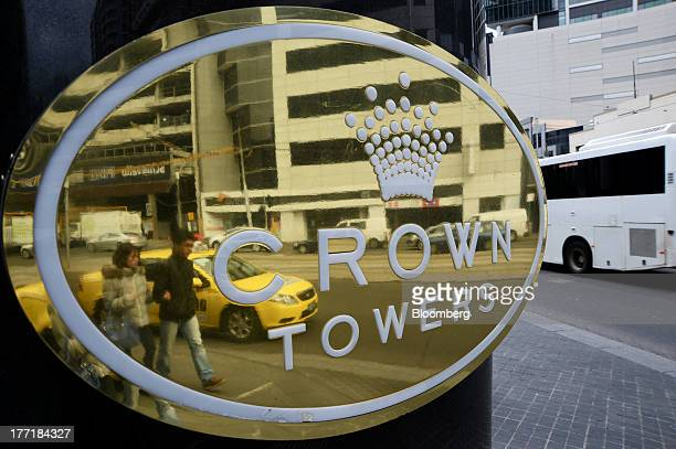 Pedestrians are reflected in a sign for the Crown Towers hotel part of the Crown Melbourne casino and entertainment complex operated by Crown Ltd in...