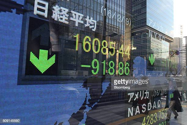 Pedestrians are reflected in an electronic board displaying the closing price of the Nikkei 225 Stock Average outside a securities firm in Tokyo...