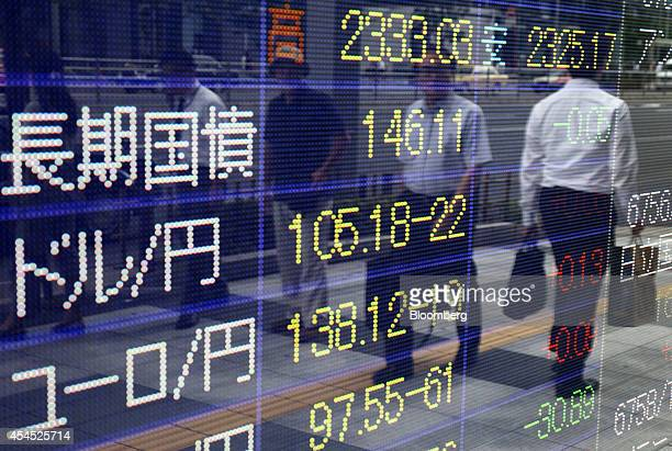 Pedestrians are reflected in an electronic stock board displaying the exchange rate of the yen against the US dollar center outside a securities firm...