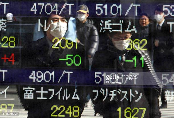 Pedestrians are reflected in an electronic stock board outside a securities firm in Tokyo Japan on Thursday March 17 2011 Japanese equities reversed...