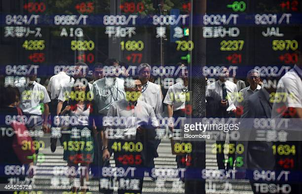 Pedestrians are reflected in an electronic stock board outside a securities firm in Tokyo Japan on Wednesday Sept 3 2014 Japan's Topix index rose on...