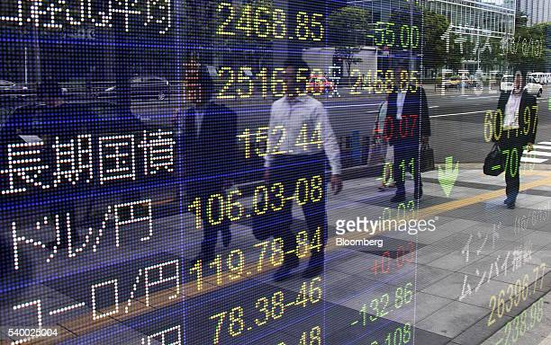 Pedestrians are reflected in an electronic stock board outside a securities firm in Tokyo Japan on Tuesday June 14 2016 Japanese stocks tumbled with...