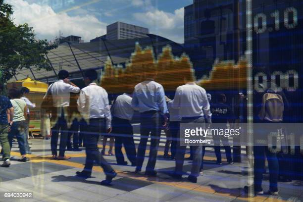 Pedestrians are reflected in an electronic stock board outside a securities firm in Tokyo Japan on Friday June 9 2017 The Topix index closed higher...