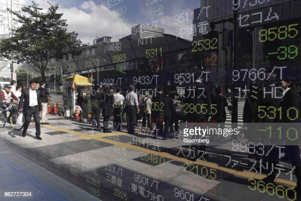 Pedestrians are reflected in an electronic stock board outside a securities firm in Tokyo Japan on Wednesday Oct 18 2017 As Prime Minister Shinzo...