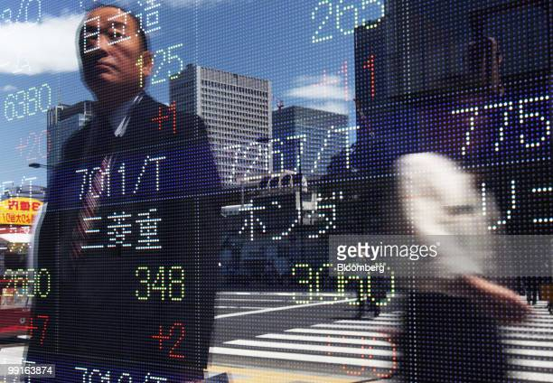 Pedestrians are reflected in an electronic stock board outside a securities firm in Tokyo Japan on Thursday May 13 2010 Asia stocks rallied the most...