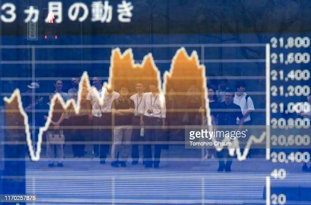 Pedestrians are reflected in an electronic stock board outside a security firm on August 26 2019 in Tokyo Japan Japanese stocks dropped and the yen...
