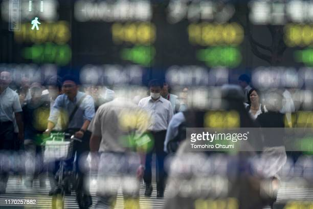 Pedestrians are reflected in an electronic stock board outside a security firm on August 26, 2019 in Tokyo, Japan. Japanese stocks dropped and the...