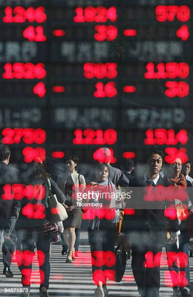 Pedestrians are reflected in an electronic stocks board in Tokyo Japan on Monday Nov12 2007 Japanese stocks dropped driving the benchmark Topix index...