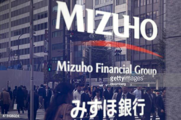 Pedestrians are reflected in signage for the Mizuho Financial Group Inc outside a Mizuho Bank Ltd branch in Tokyo Japan on Friday Nov 10 2017 Mizuho...