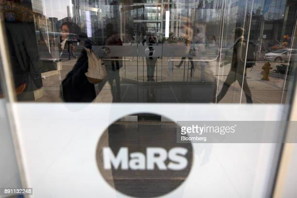 Pedestrians are reflected in the front doors to the MaRS Discovery District in Toronto Ontario Canada on Monday Dec 4 2017 A halfcentury ago Canadian...