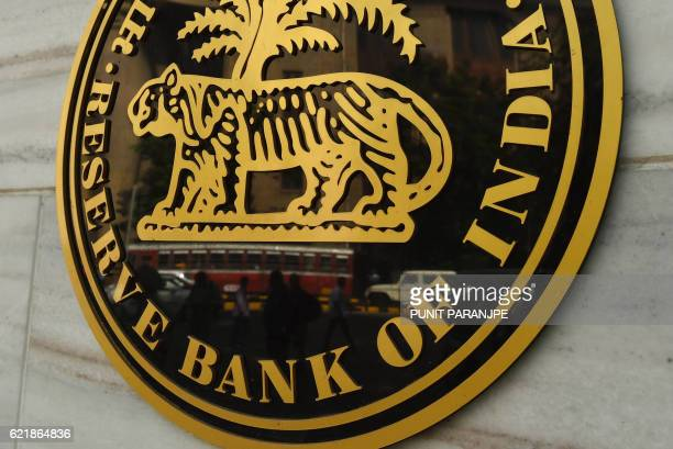 Pedestrians are reflected in the logo of India's central bank the Reserve Bank of India in Mumbai on November 9 2016 Indian Prime Minister Narendra...