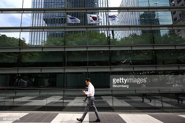 Pedestrians are reflected in the Samsung CT Corp headquarters as they walk past in Seoul South Korea on Friday July 17 2015 Samsung Group prevailed...