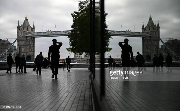 Pedestrians are reflected in the window of a building as they walk near Tower Bridge in London on September 15, 2021. - British annual inflation...