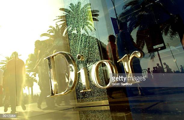 Pedestrians are reflected in the window of a Dior shop as they walk past during the 56th International Cannes Film Festival 2003 May 19, 2003 in...