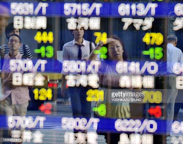 Pedestrians are reflected in the window of a stock brokerage showing share prices in Tokyo on September 12 2011 Japan's share prices fell 20199...