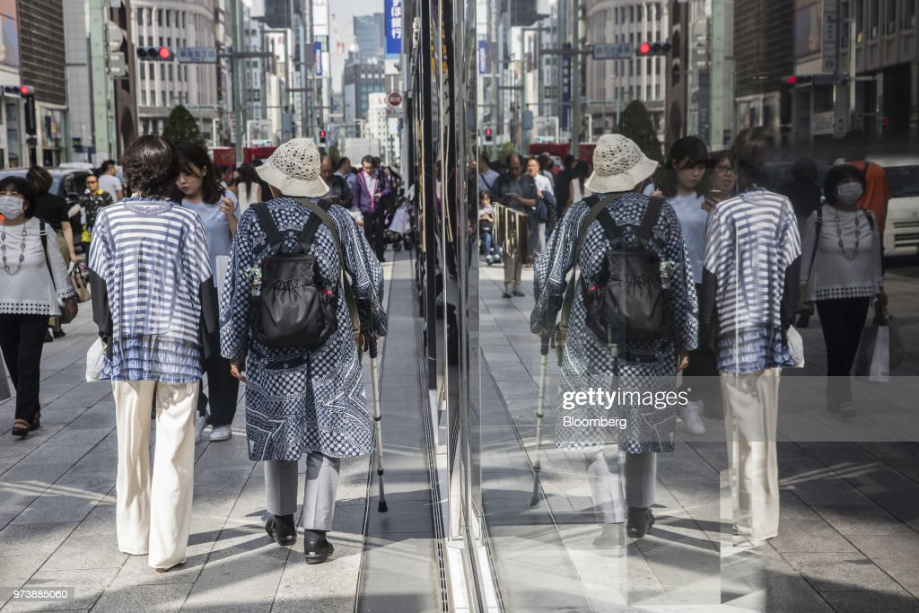 Pedestrians are reflected in windows at the Ginza district of Tokyo, Japan, on Friday, May 25, 2018. The savings-rich elderly spend about 9.7 trillion yen ($87 billion) a year on their offspring and such spending last year accounted for about a third of the modest growth in total consumption, according to Hiromichi Shirakawa, chief Japan economist at Credit Suisse Group. Photographer: Shiho Fukada/Bloomberg via Getty Images